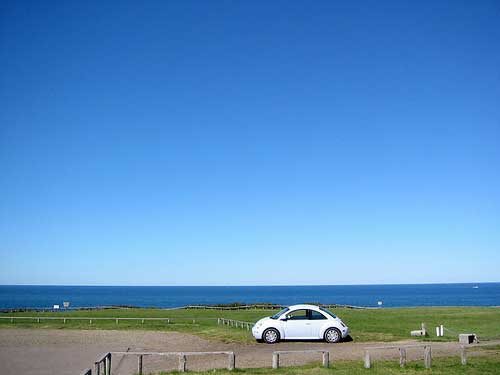 Car at fields and sea, Hokkaido, Japan
